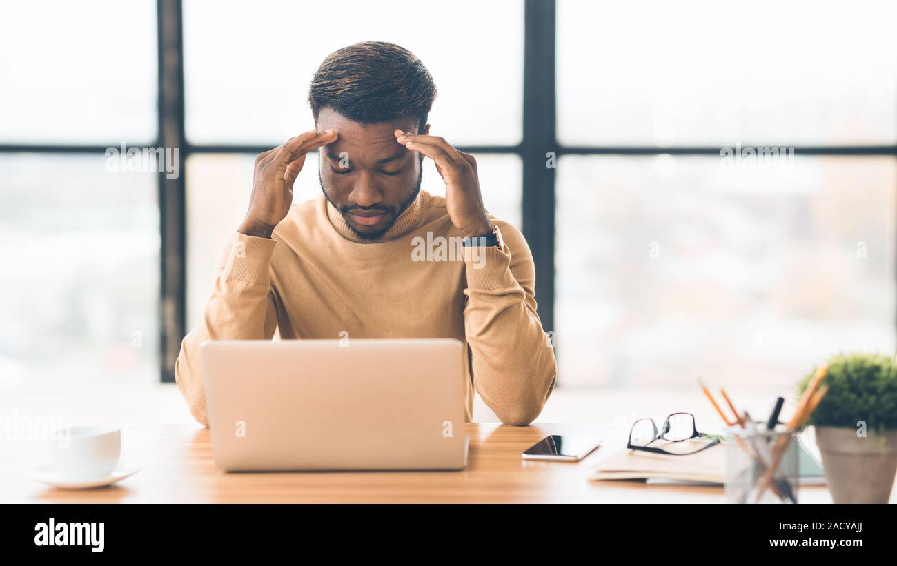 Exhausted millennial black businessman having migraine attack Stock Photo