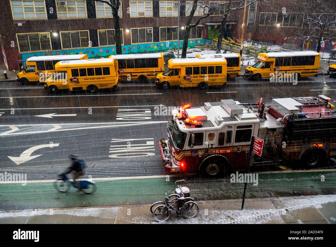 School buses line up in front of PS 33 in Chelsea in New York in anticipation of dismissal on Monday, December 2, 2019. New York is expected to receive between 1 and 3 inches of snow during this first storm of the season. (© Richard B. Levine) Stock Photo