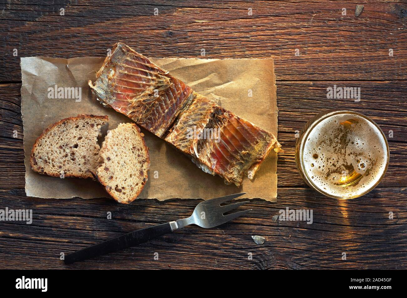 Fish on a paper, bread and glass of beer on old wooden table, top view Stock Photo