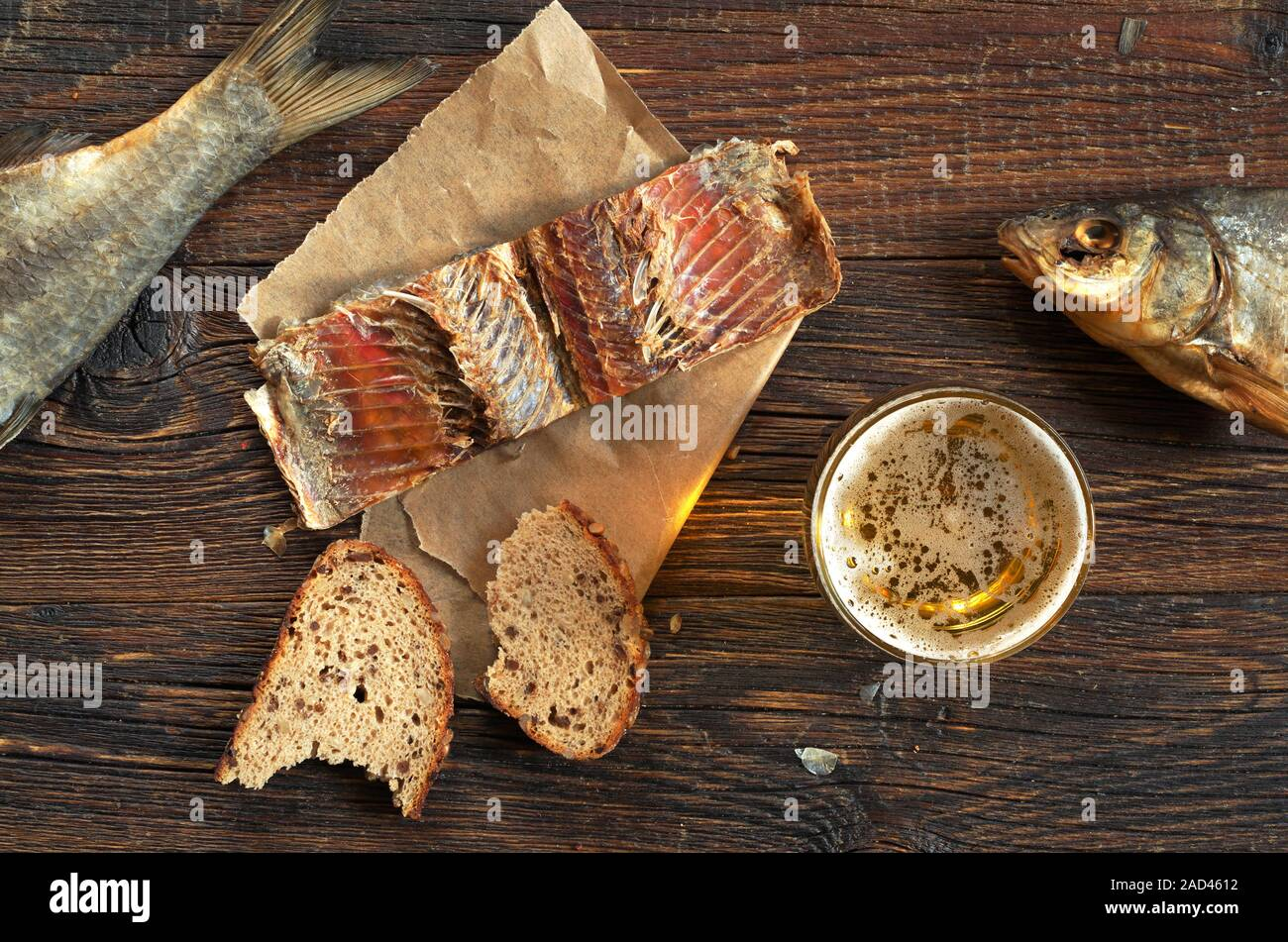 Glass of beer, salted fish and bread on old wooden table, top view Stock Photo