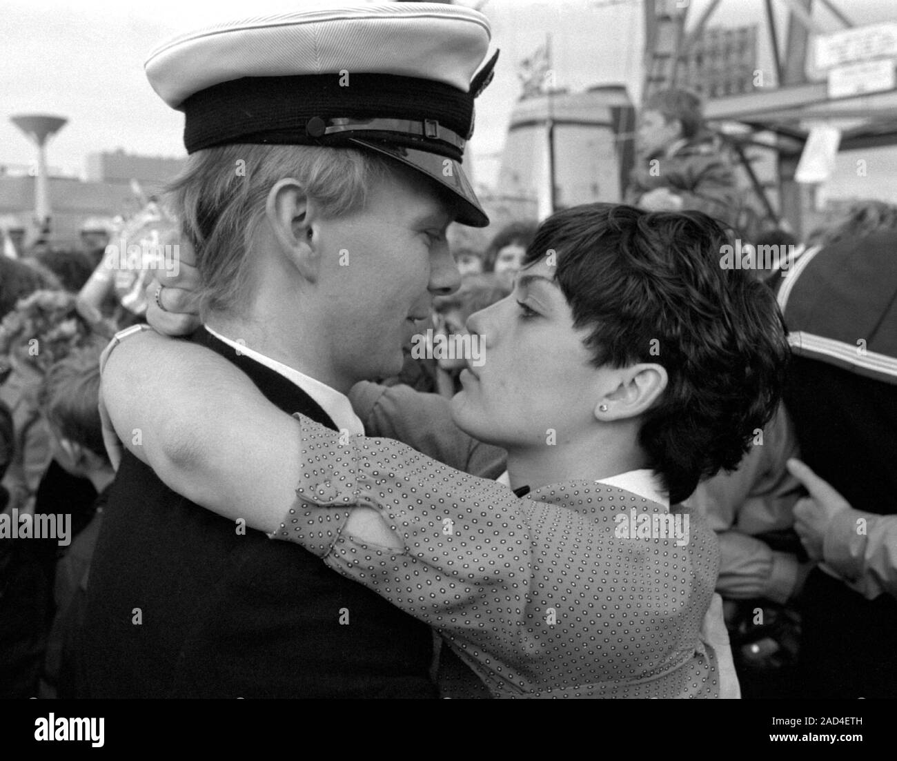 AJAXNETPHOTO. 19TH JUNE, 1982. PORTSMOUTH, ENGLAND. - FALKLANDS VETERAN - A YOUNG OFFICER  OFTHE SHEFFIELD CLASS (TYPE 42/1&2) DESTROYER HMS GLASGOW RECEIVES A WARM WELCOME HOME WHEN HIS BOMB DAMAGED SHIP RETURNED TO PORTSMOUTH IN 1982.  PHOTO:JONATHAN EASTLAND/AJAX.  REF:HD NA GLAS 82 8A. Stock Photo