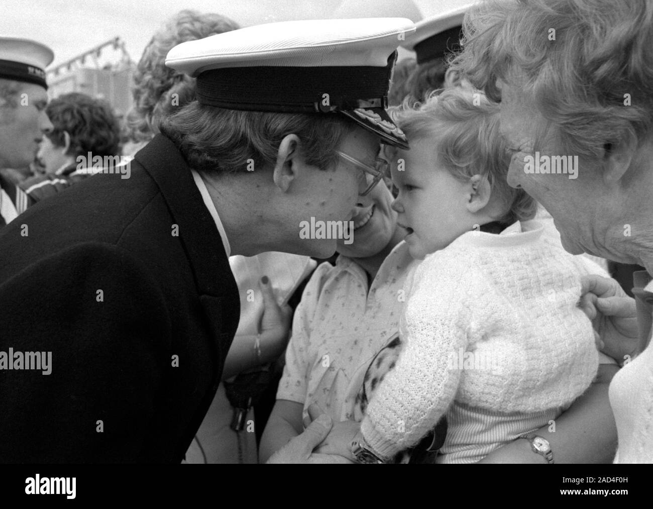AJAXNETPHOTO. 19TH JUNE, 1982.PORTSMOUTH, ENGLAND. - FALKLANDS VETERAN - AN OFFICER OF THE SHEFFIELD CLASS (TYPE 42/1&2) DESTROYER HMS GLASGOW RECEIVES A WARM WELCOME FROM HIS YOUNG FAMILY WHEN HIS BOMB DAMAGED SHIP RETURNED TO PORTSMOUTH IN 1982.  PHOTO:JONATHAN EASTLAND/AJAX.  REF:HD NA GLAS 82 22. Stock Photo