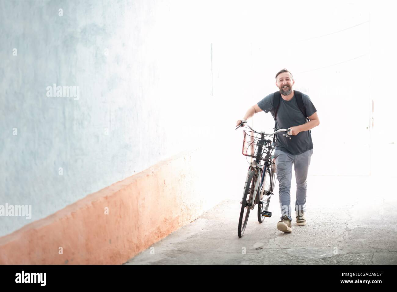 hipster man with a backpack pushing a retro bicycle Stock Photo