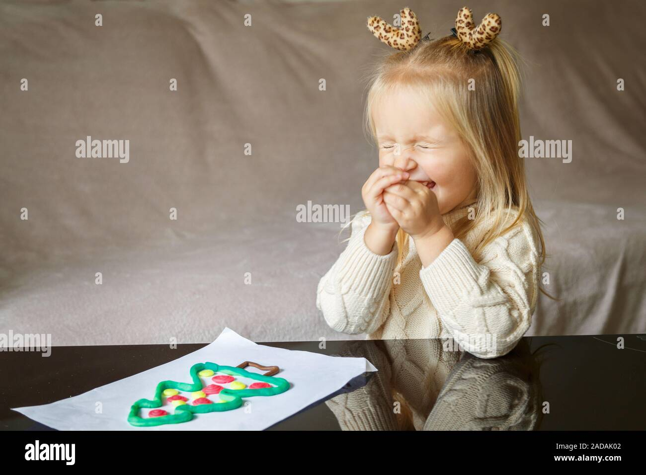 Adorable little girl with blonde hair playing with clay and making christmas tree at home Stock Photo
