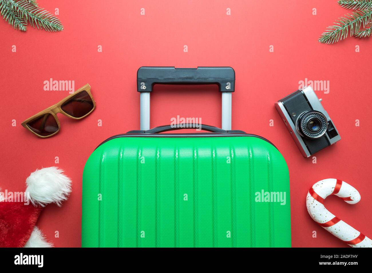 Christmas holiday minimal creative composition made of suitcase, sunglasses,Santa hat, candy cane, retro photo camera and fir branches on red backgrou Stock Photo