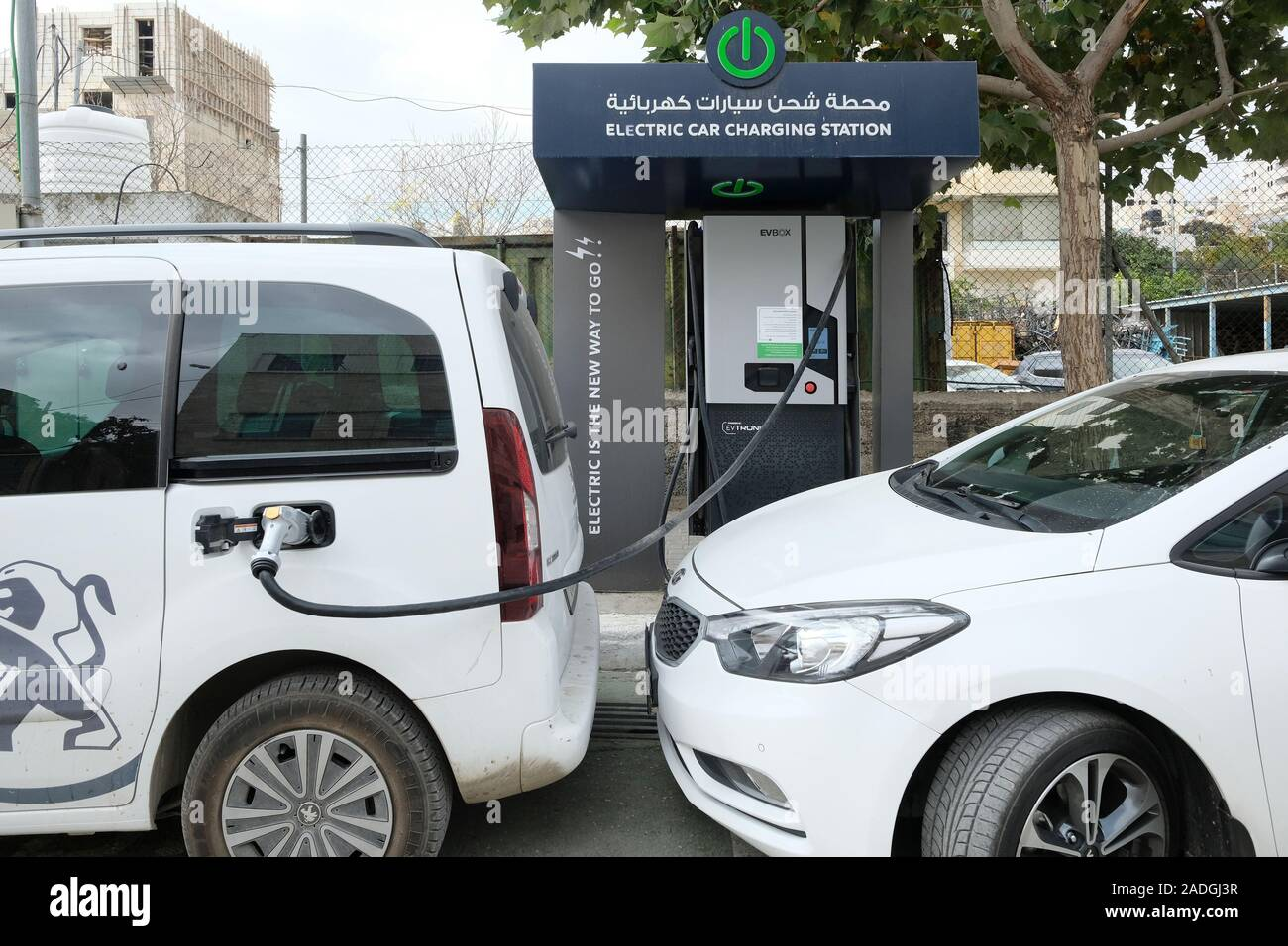 Car charging from an on-street electric car charging station in the city of Hebron in the West Bank, Palestinian Territories. Stock Photo