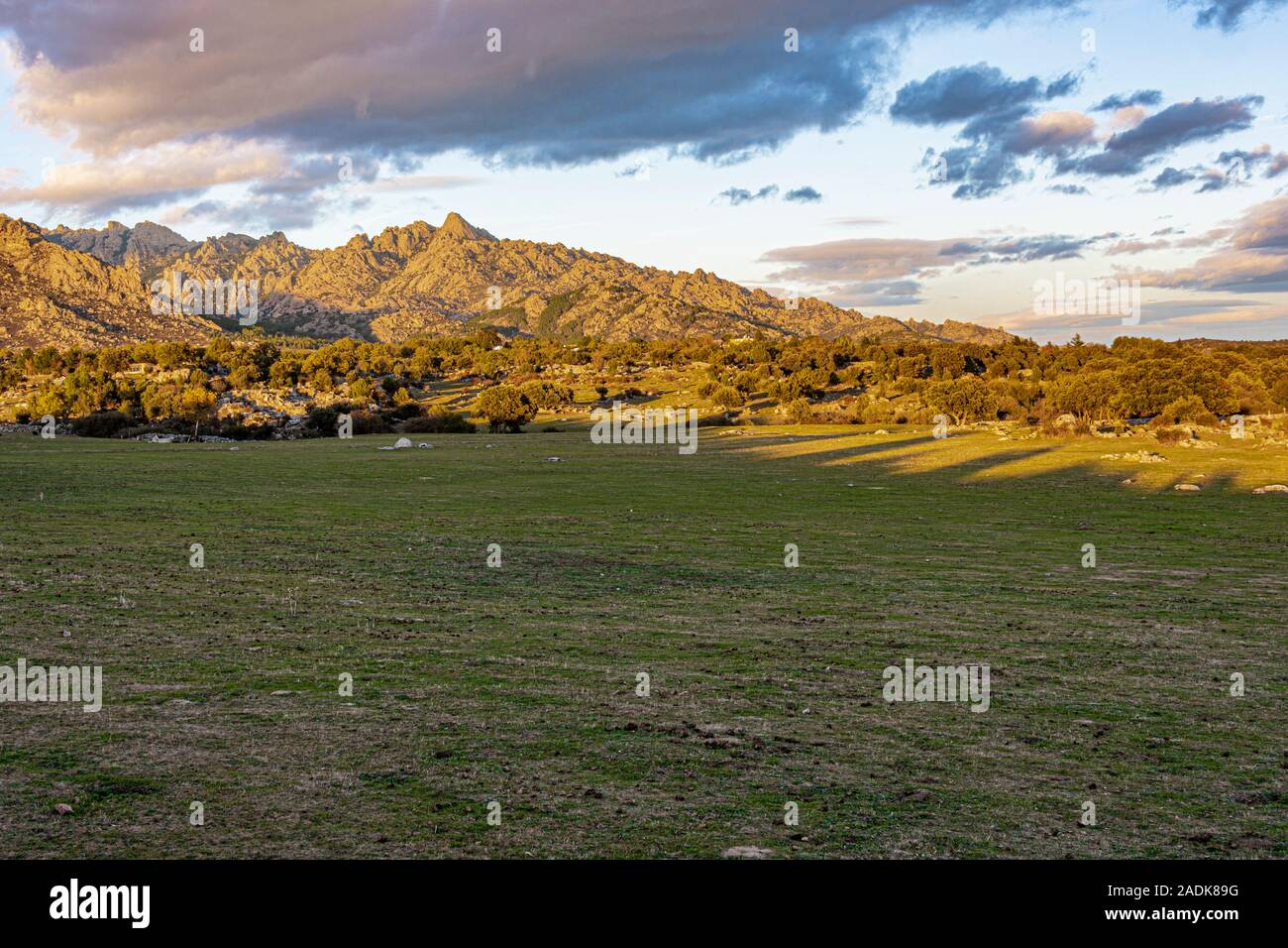 View of the meadows and mountains one day with clouds at sunset in the Sierra de Guadarrama. madrid Spain Stock Photo