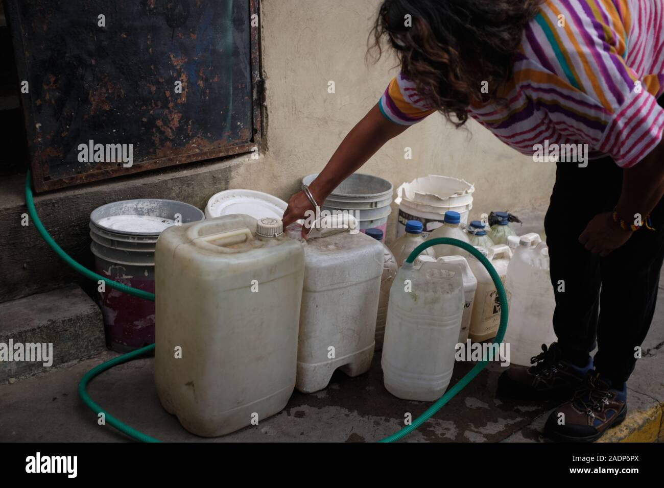 Caracas, Miranda, Venezuela. 29th Nov, 2019. Aura filling the water contaners with the water from Aura's sister's house.Aura Graciela Sarmiento, age 56, and her husband Jose Alberto Abreu, age 62, have not had running water at their house in 4 years. Aura works in a store selling office furniture, and Jose is a mechanic. They live in the neighborhood of Altos de Lidice in Caracas Venezuela. Altos de Lidice is a historic Chavista neighborhood. However, Aura is pro-Opposition, and has never supported the Chavez regime even though she has lived in this pro-Chavez/Maduro barrio her whole life Stock Photo