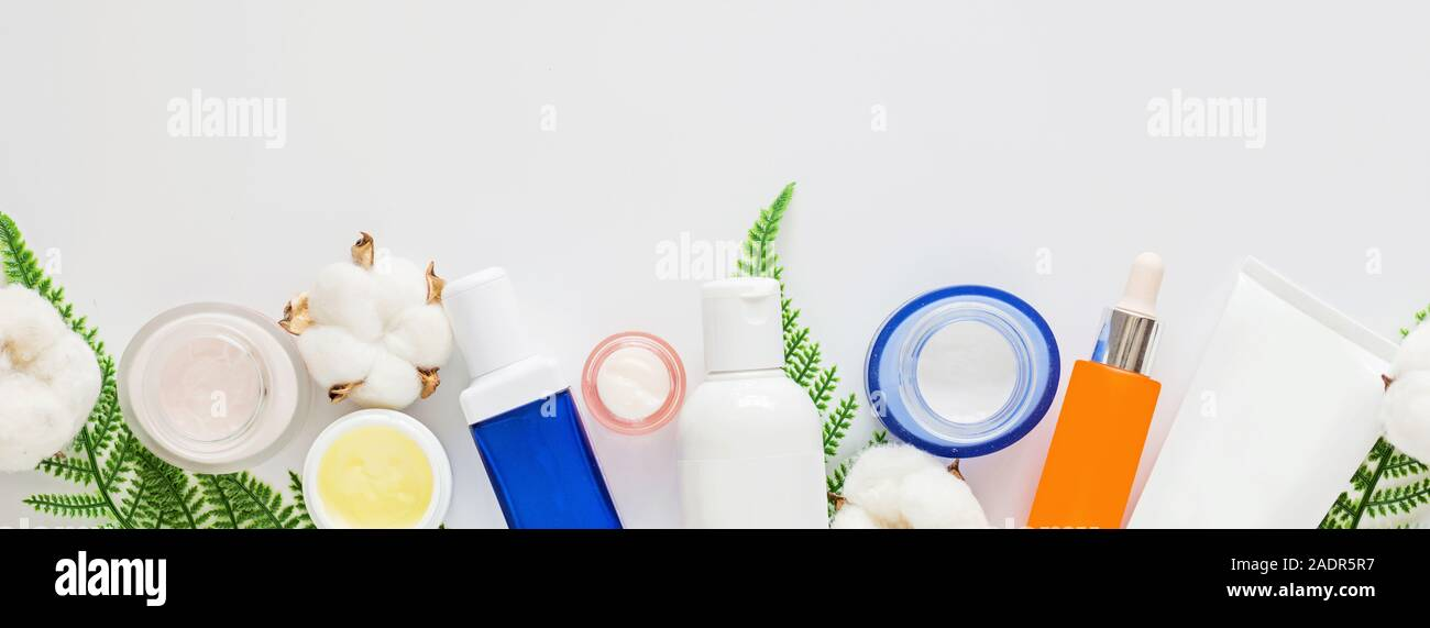Flat lay with Natural organic cosmetics: serum, cream on white background with green leaves. Copy space, Skincare, cosmetology, dermatology concept. S Stock Photo