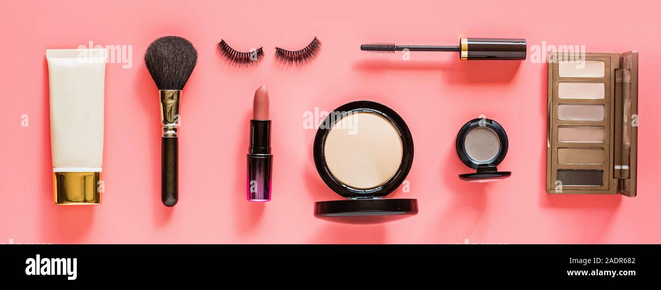 Make up items on pink color background. Horizontal web banner. Set of luxury decorative cosmetics flat lay, top view, mock up, template. Minimal style Stock Photo