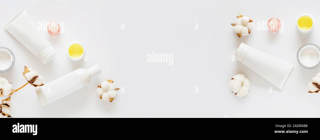 Flat lay with Natural organic cosmetics: tonic, cream on white background with cotton flowers. Skincare, cosmetology, dermatology concept. Spa certifi Stock Photo