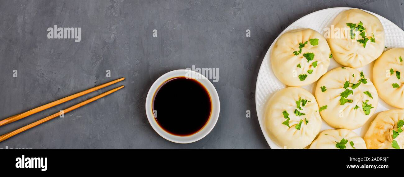 Close up of Chinese steamed dumplings with soy sauce on gray concrete background. Flat lay, top view, overhead, mock up, template. Asian food concept. Stock Photo