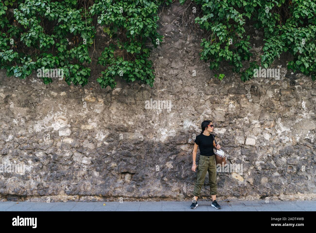 Active young woman with her bag hanging, next to a stone wall looking Stock Photo