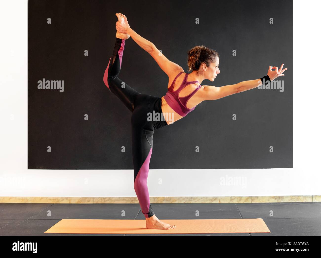 Young woman performing a Natarajasana yoga pose, or Lord of the ...