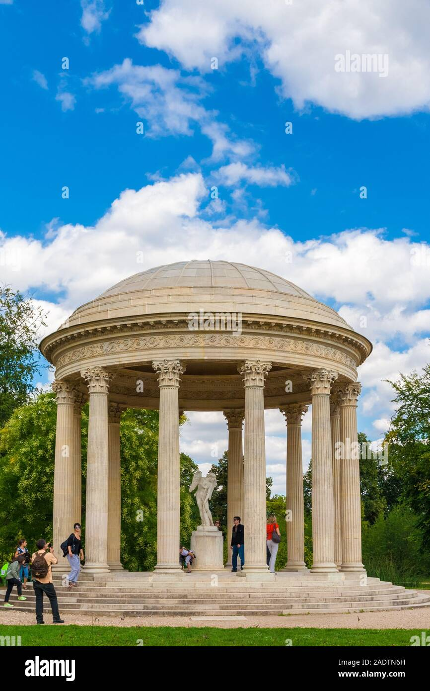 Great portrait view of the Love Monument in the Anglo-Oriental Garden in the Petit Trianon in Versailles. Visitors are posing with the centrepiece... Stock Photo