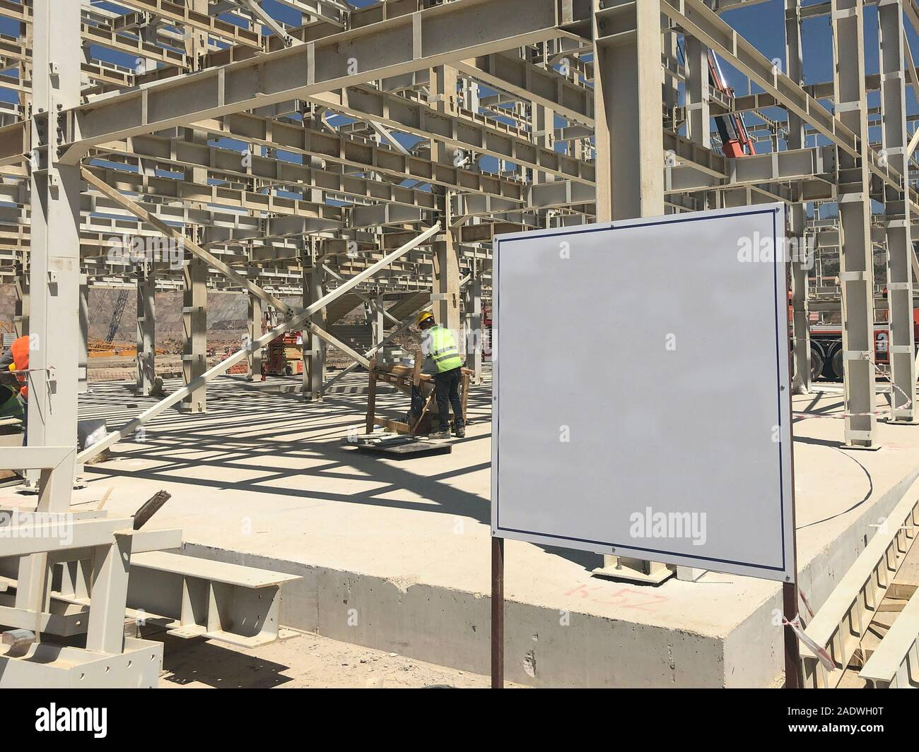 Object under construction stand at the construction site. Blank display board against prefabricated multi-storey building at the background Stock Photo