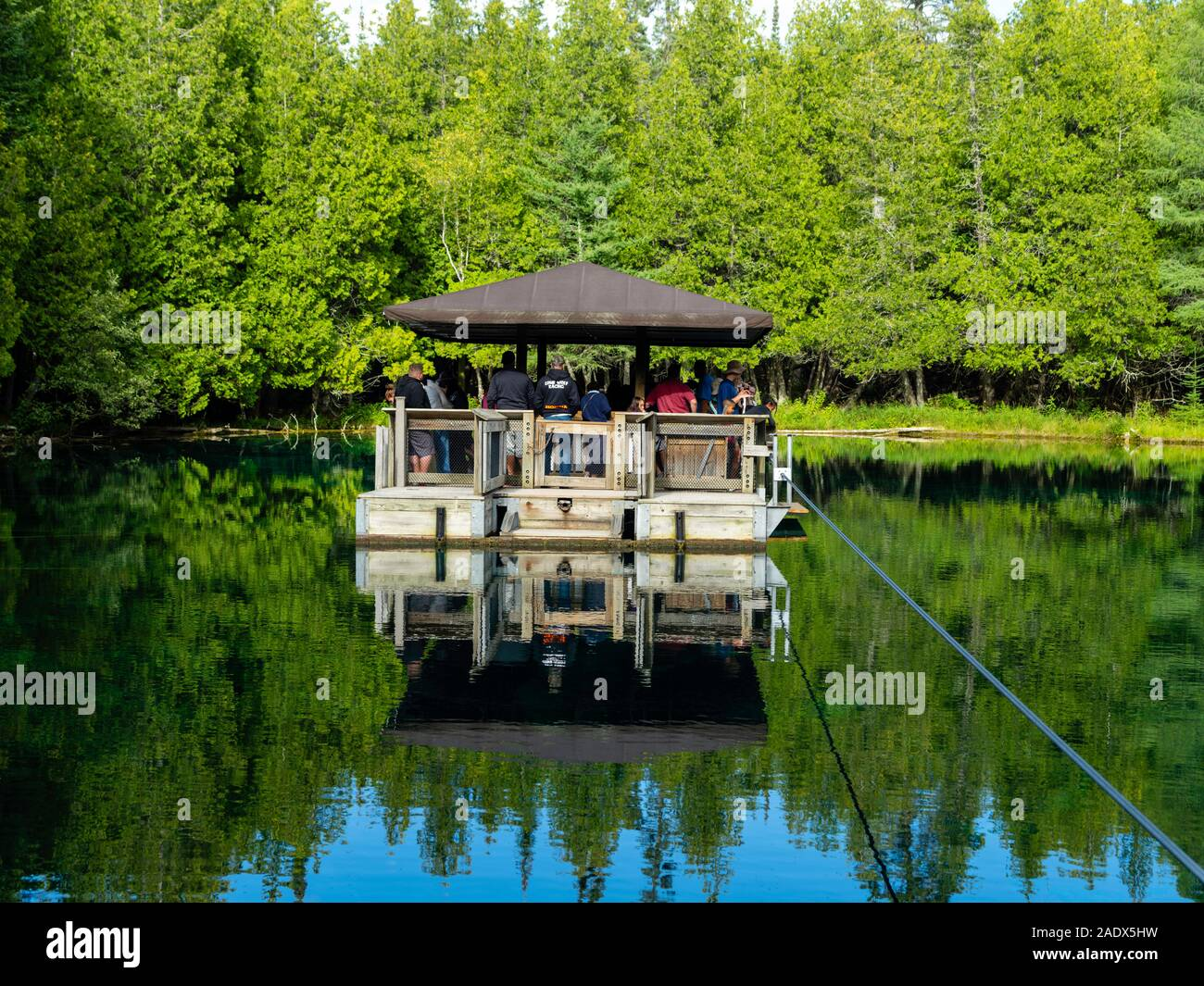 Tourists venture out on a barge to view trout in crystal clear water in Kitch-iti-kipi/Big Spring at Palms Book State Park, near Manistique, Michigan, Stock Photo