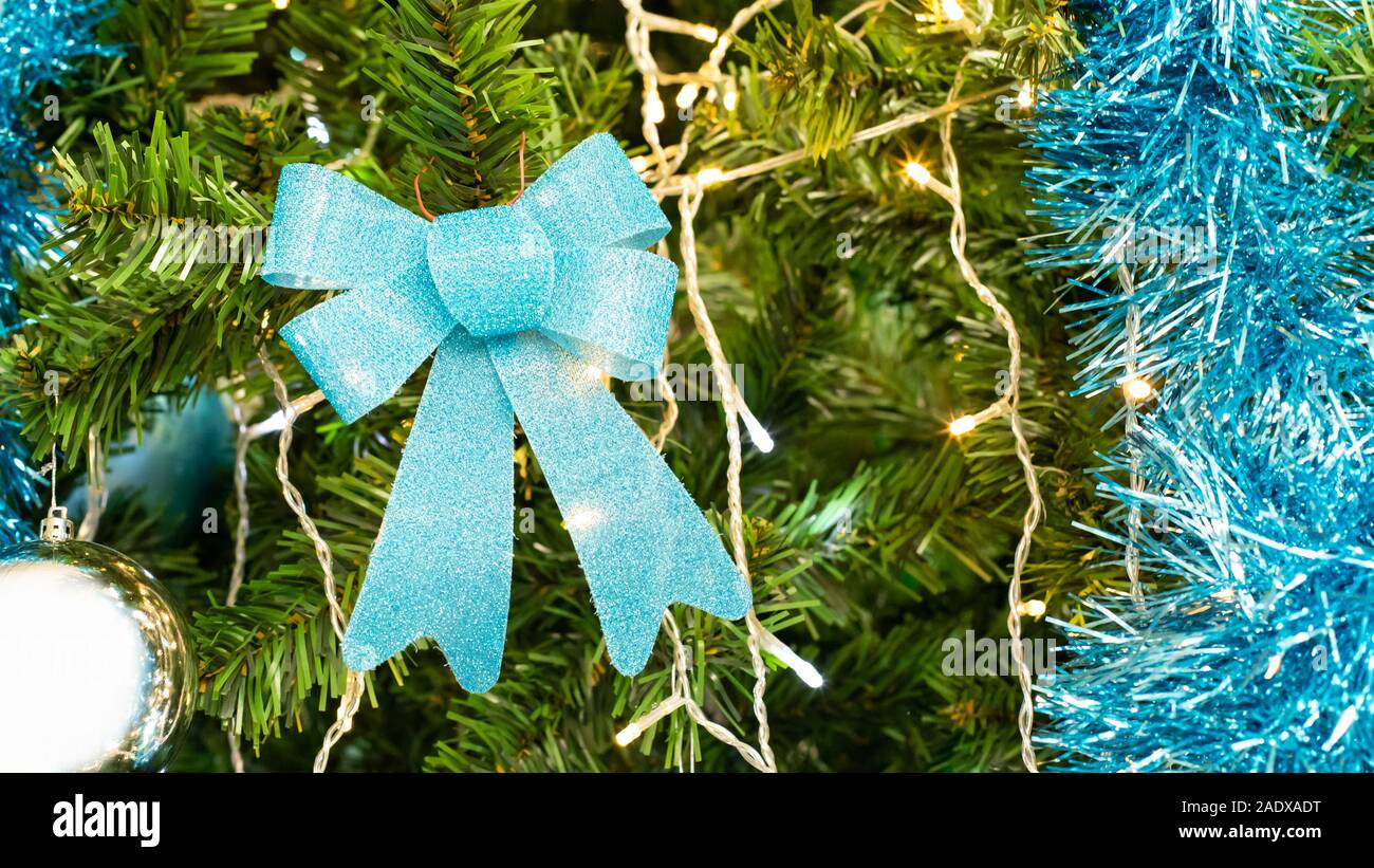 blue bow on a christmas tree branch with a garland festive christmas decoration artificial eco tree with plastic needles backdrop wallpaper 2ADXADT