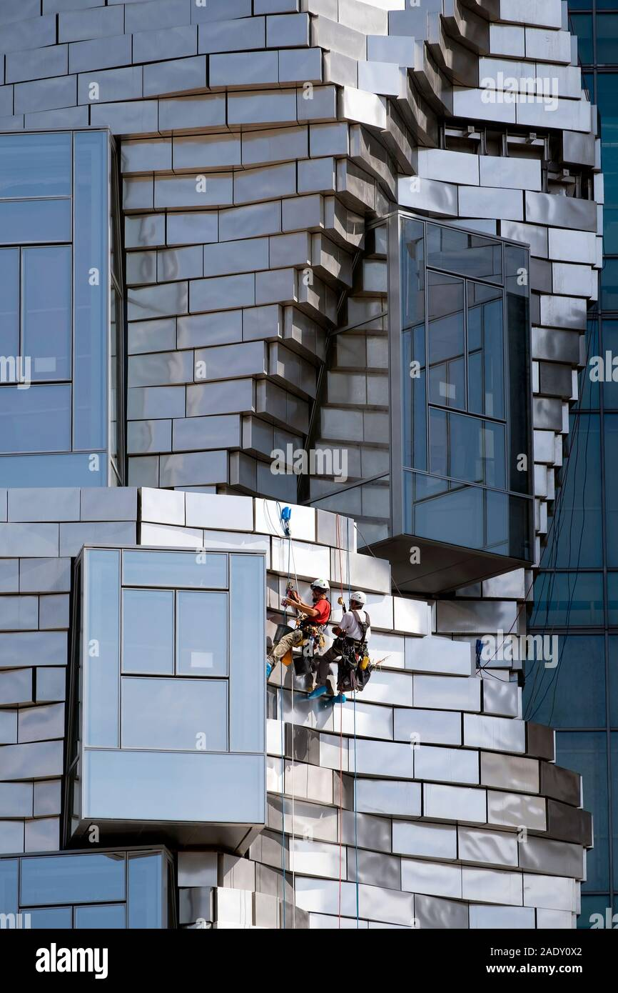 Two workers hanging / abseiling / rappelling while cleaning panels on  Frank Gehry LUMA Foundation building, Luma Arles Cultural Centre, Arles, France Stock Photo