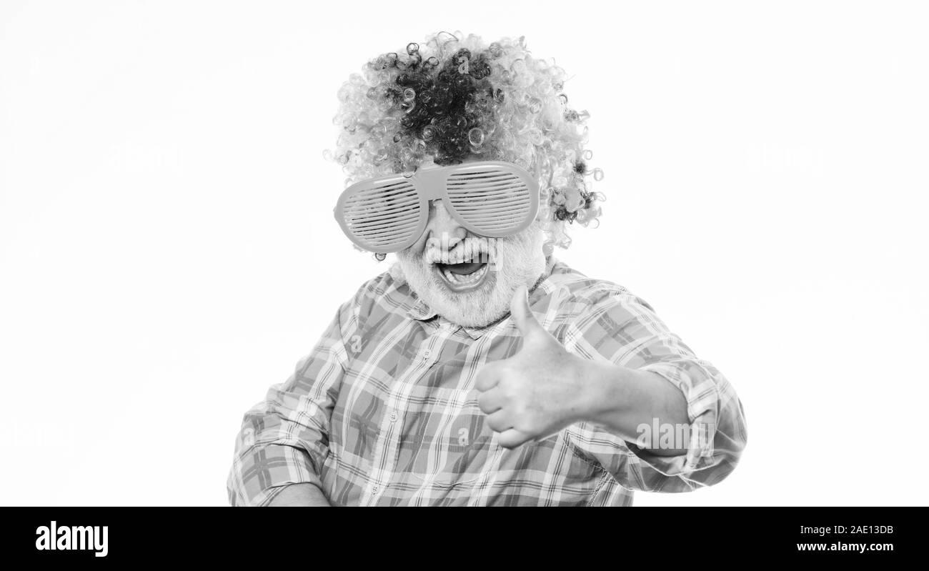Funny lifestyle. Fun and entertainment. Comic grandfather concept. Nice joke. Grandpa always fun. Man senior bearded cheerful person wear colorful wig and sunglasses. Elderly clown. Having fun. Stock Photo