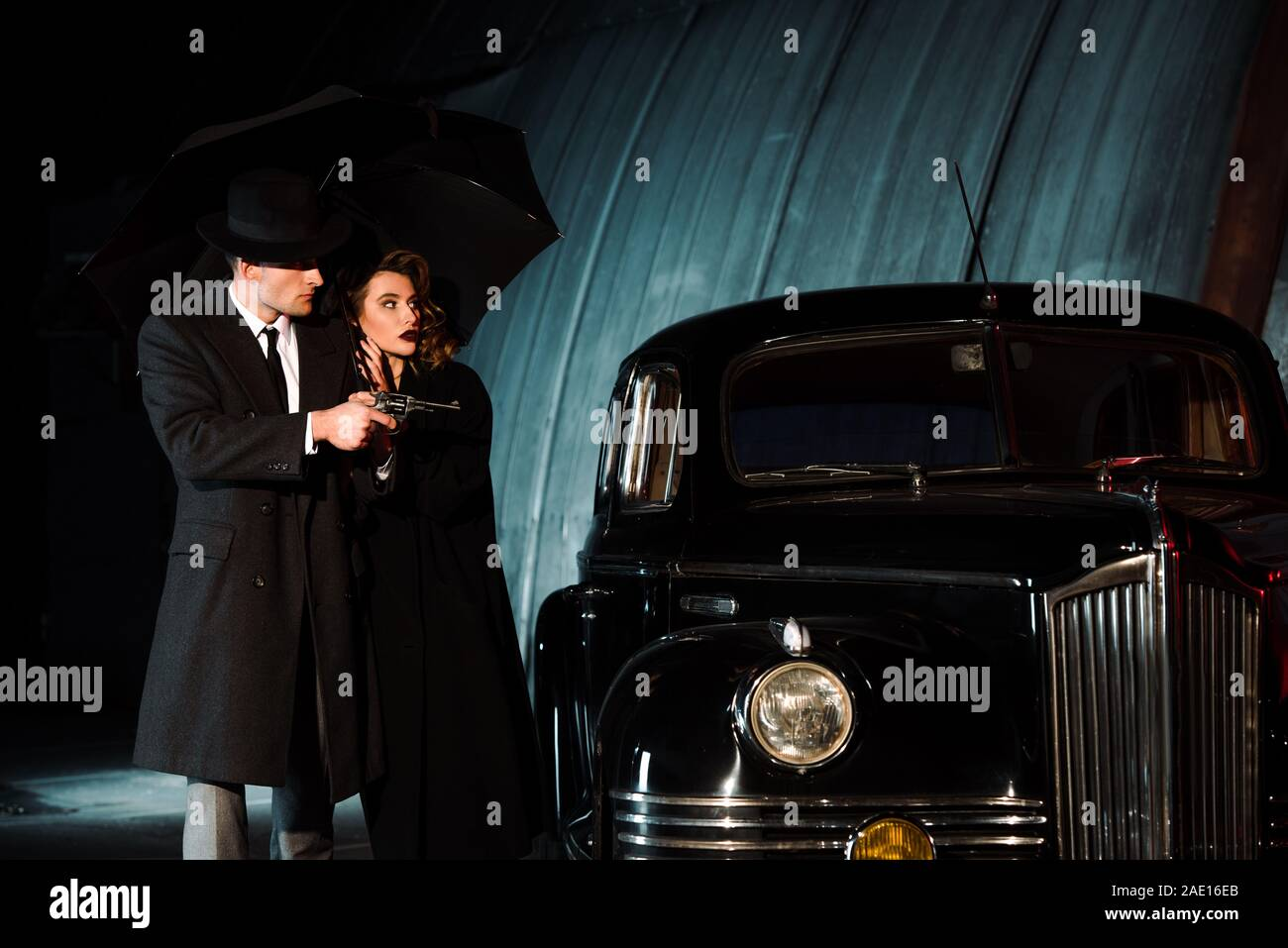 dangerous man in hat holding gun and umbrella near woman and retro car Stock Photo