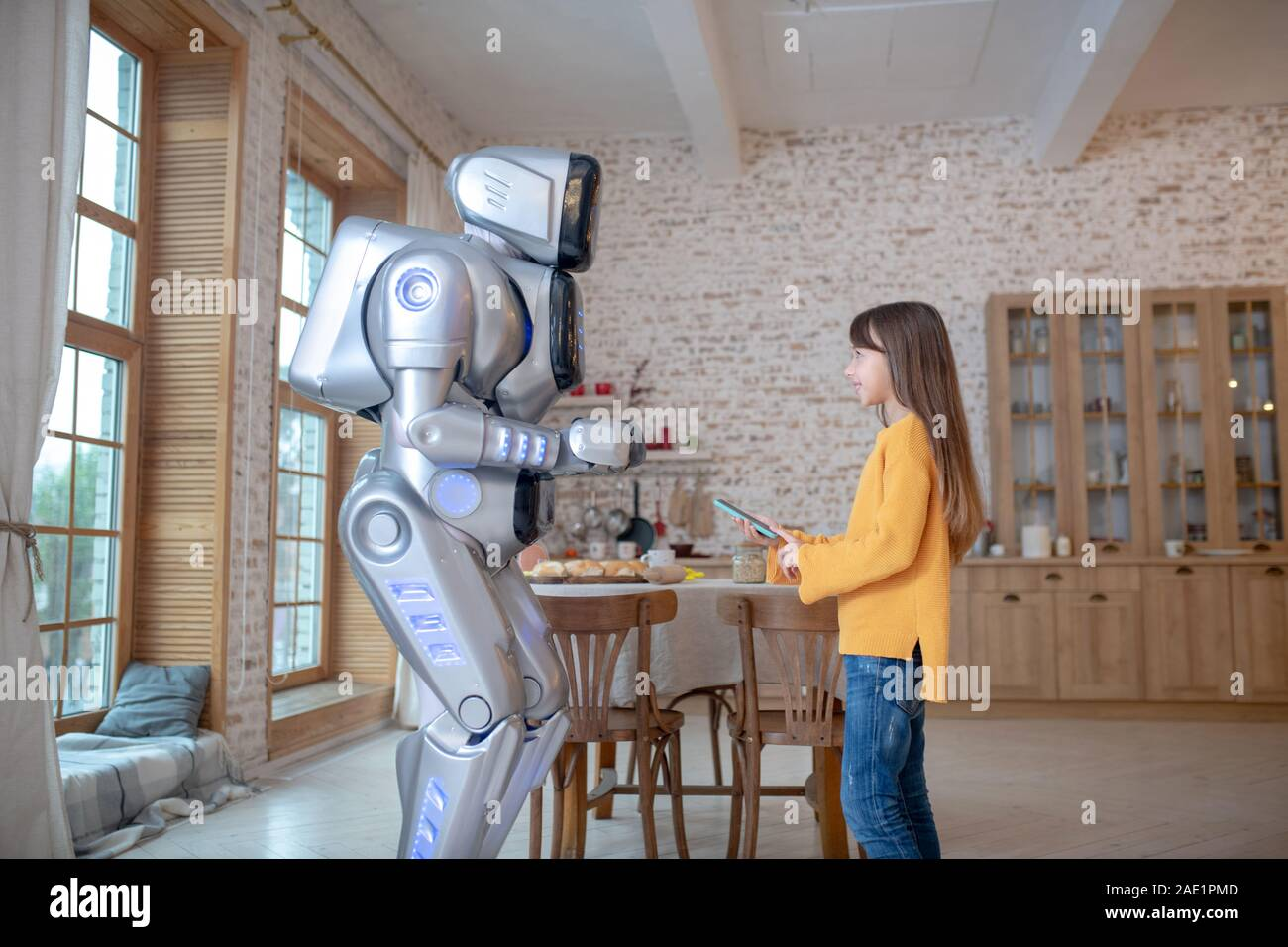Robot And A Cute Girl Talking In The Kitchen Stock Photo Alamy
