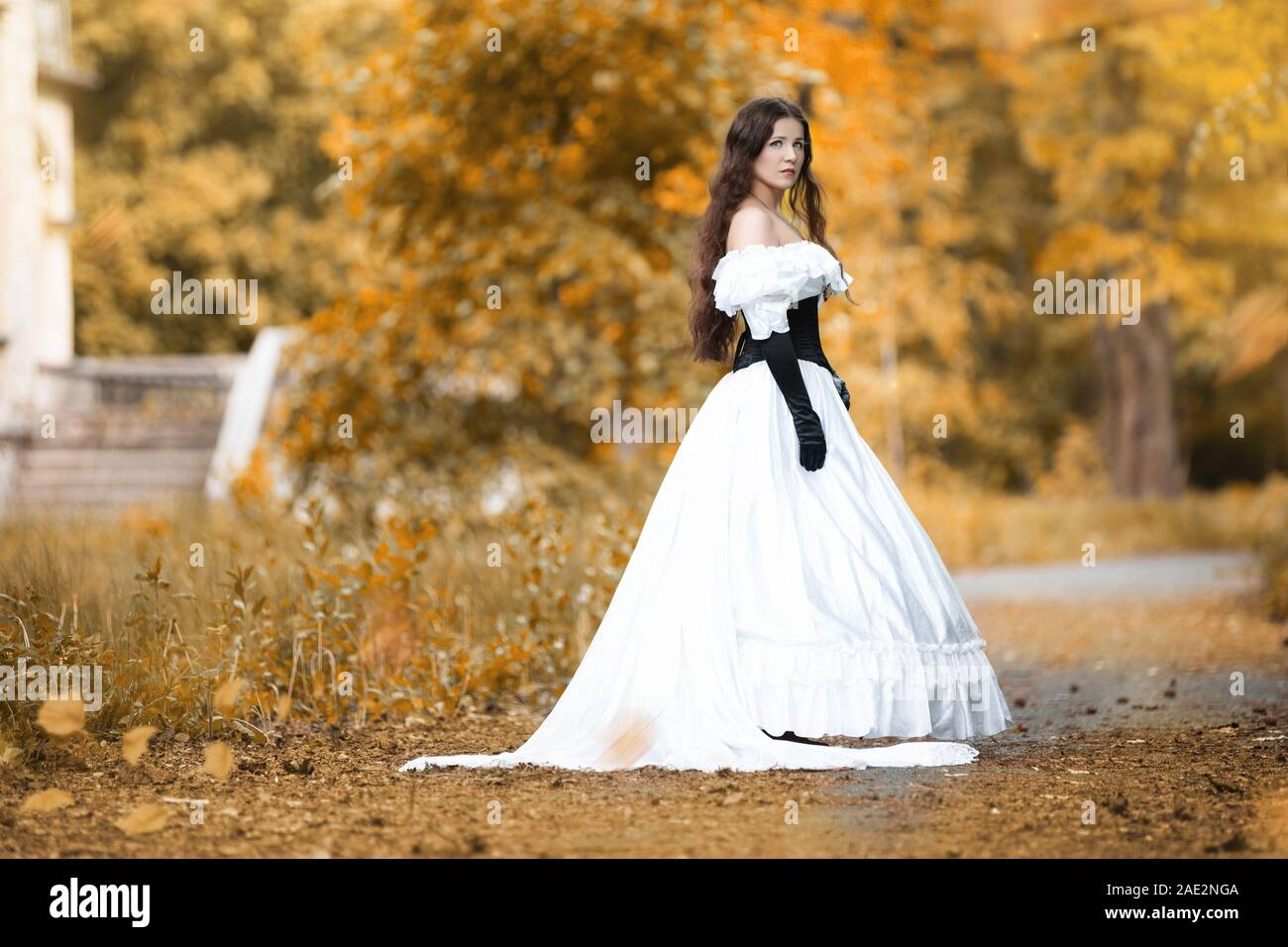 Woman in a white Victorian dress in an autumn park Stock Photo