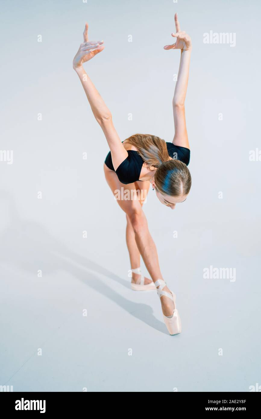 Professional ballerina dancing ballet on white cyclorama.Beautiful young girl with long hair wearing black suit isolated on white studio background. Stock Photo