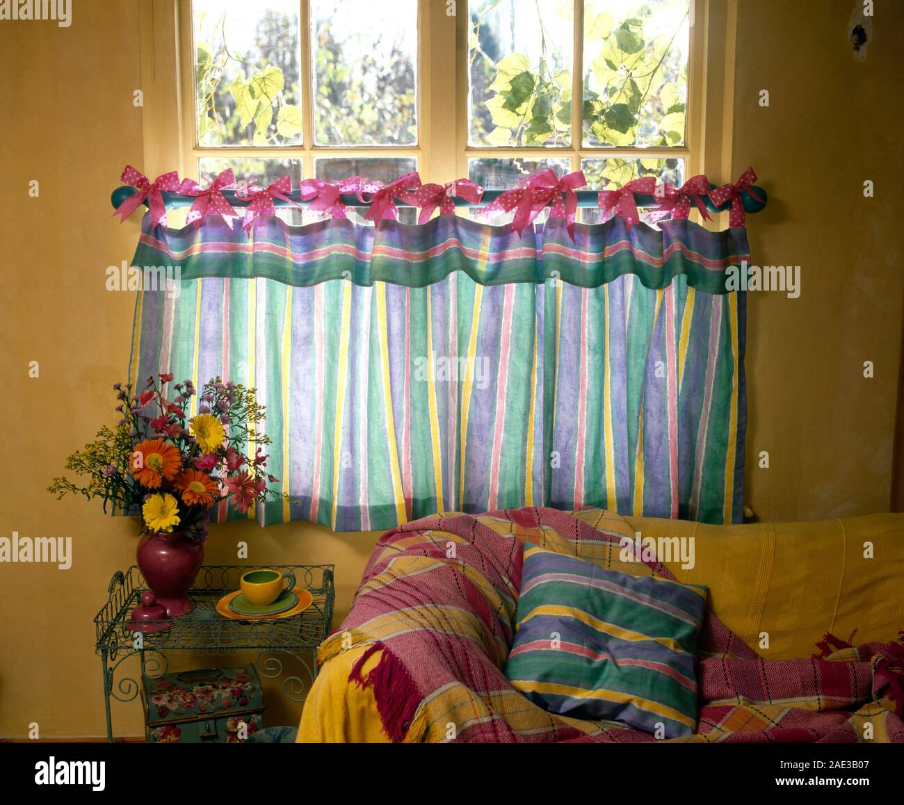 Colourful Striped Cafe Curtains Tied With Pink Bows Onto A Brass Rod On Window In Economy Style Cottage Living Room Stock Photo Alamy
