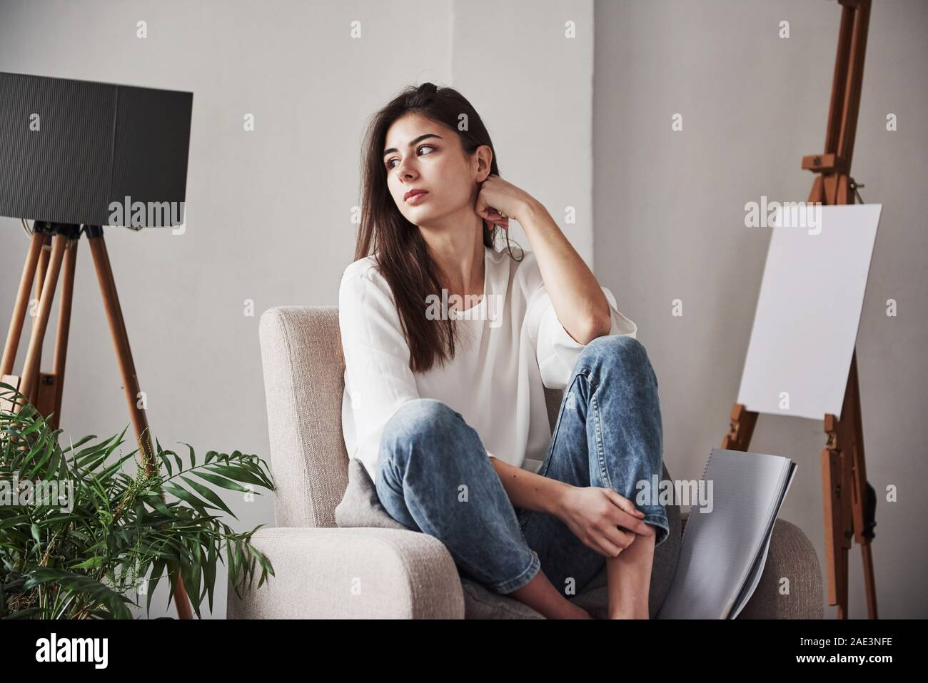 Relaxed woman sitting on the chair and looking to the side. Young brunette in the room with white walls and daylight that comes from the window Stock Photo