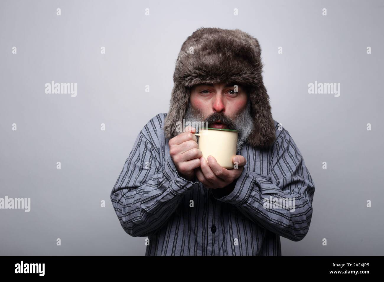 Sick man with pajamas and with a cap blowing a cup of hot tea on a gray background Stock Photo