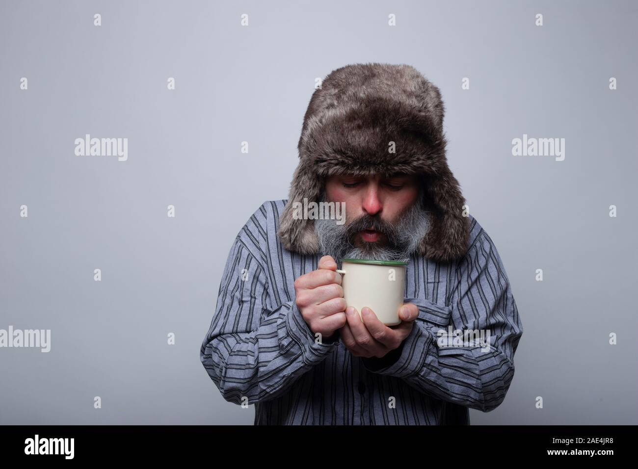 Flu sick man with pajamas and with a cap blowing a cup of hot tea on a gray background. Health concept. Stock Photo