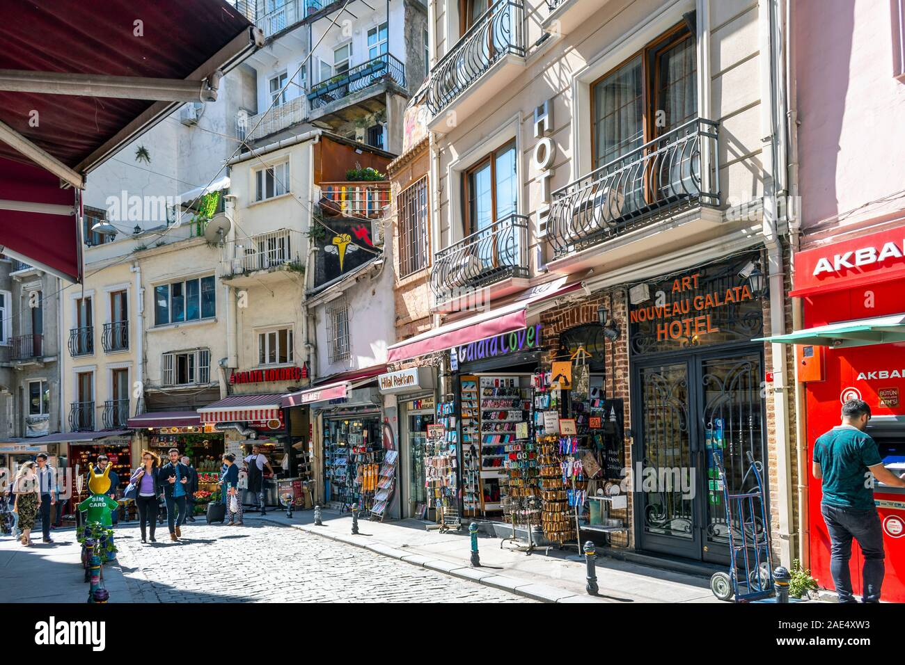 Tourists walk past colorful souvenir and gift shops and cafes on a busy summer day in the Galata Karakoy district of Istanbul, Turkey Stock Photo