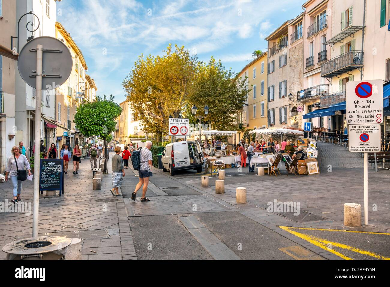 Tourists and local French enjoy a summer morning at an outdoor flea market in the historic seaside town of Antibes, France, on the French Riviera. Stock Photo