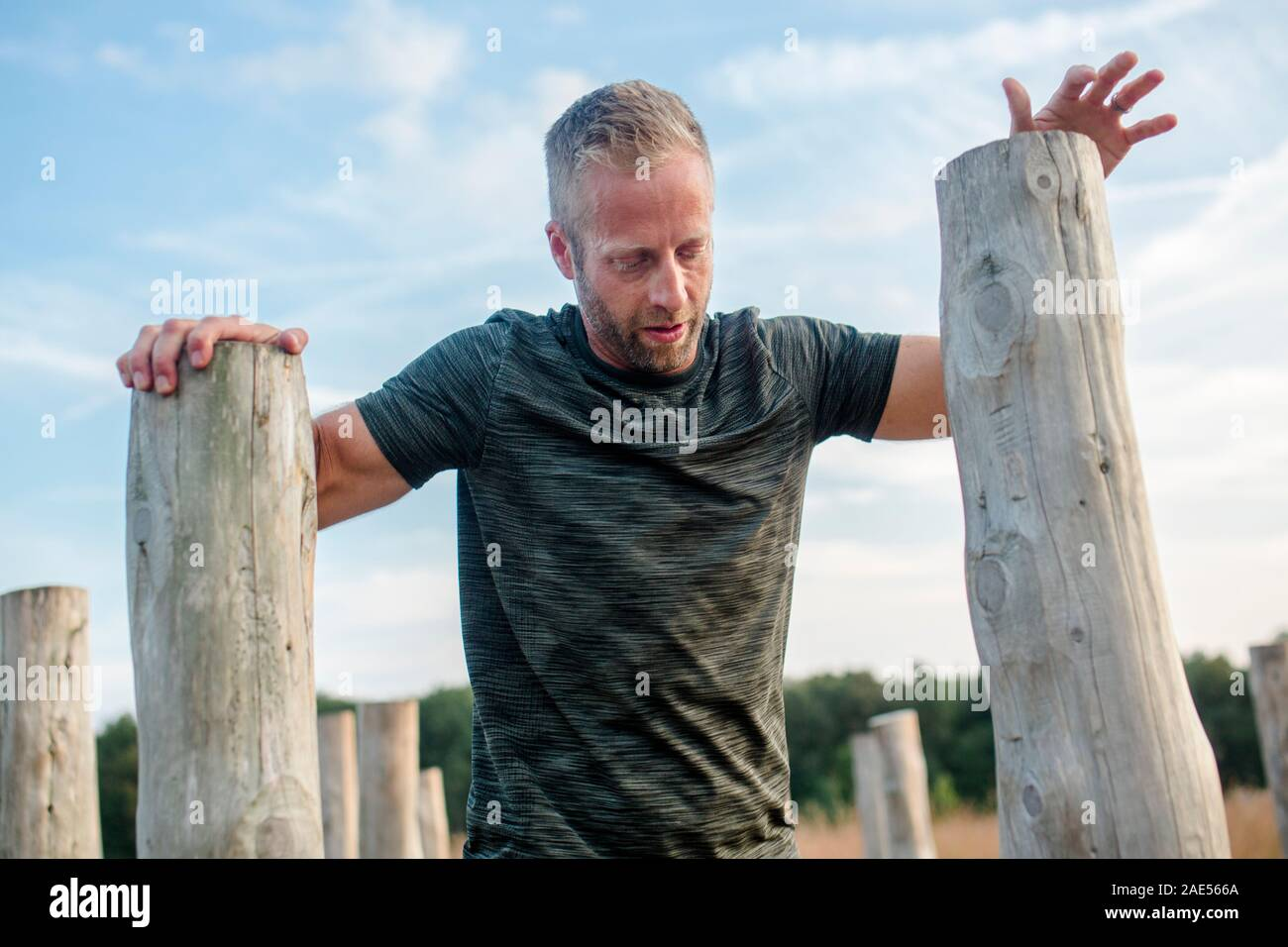 Top-half of man leaning on wood poles on obstacle course Stock Photo