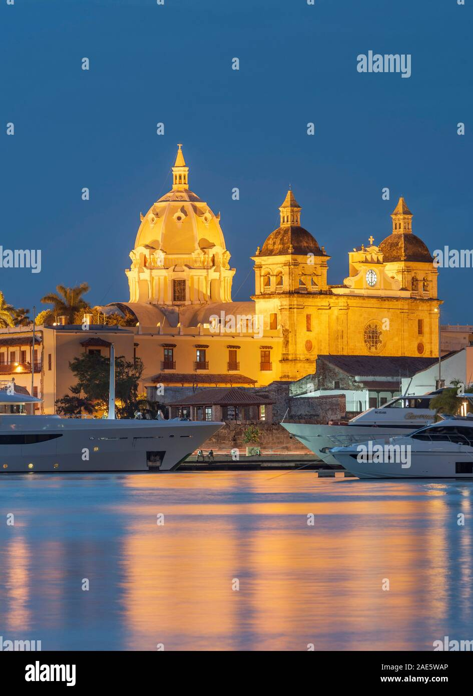 Dusk view of boats moored alongside the historic buildings of the walled old city of Cartagena in Colombia. Stock Photo