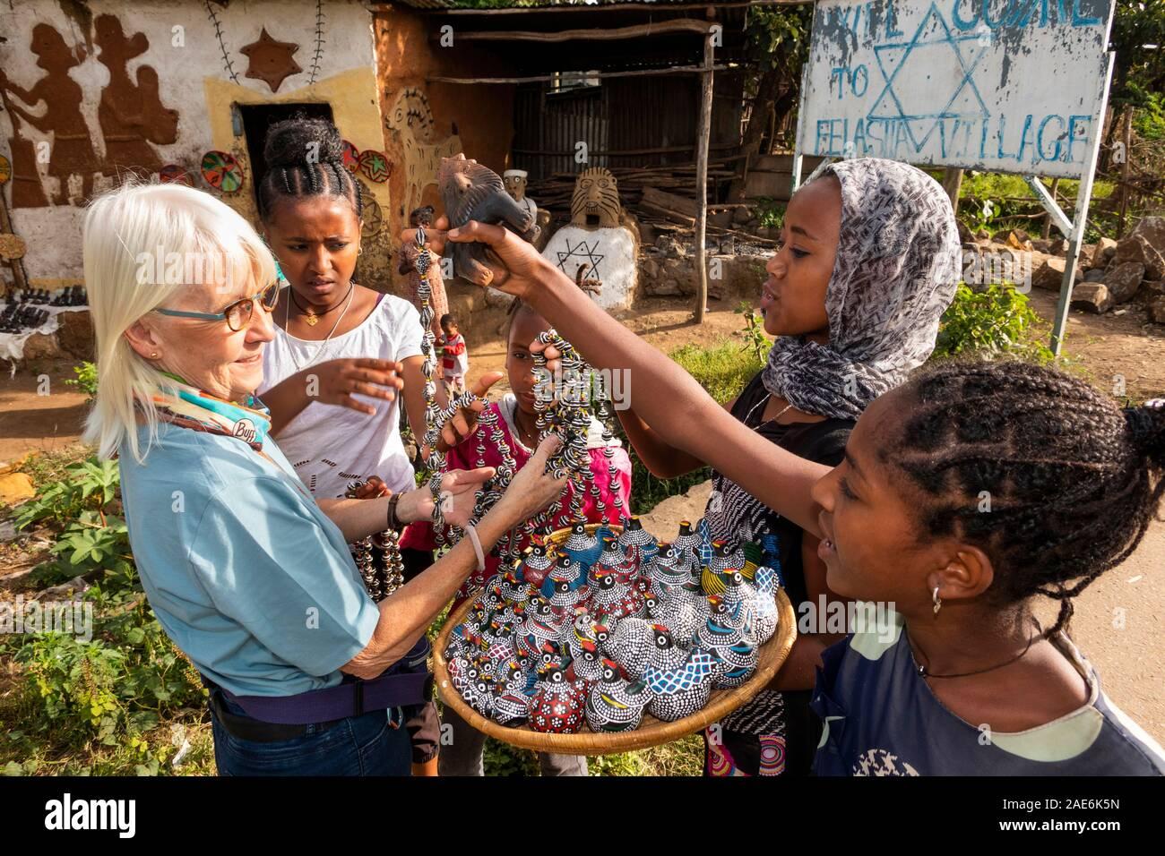 Ethiopia, Amhara Region, Gondar, Wolleka Falasha Jewish Village, children selling souvenirs to senior tourist Stock Photo