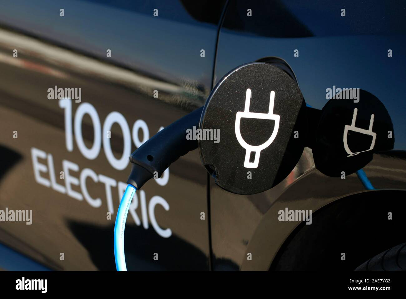 An Electric car is being charged in a charging station Stock Photo