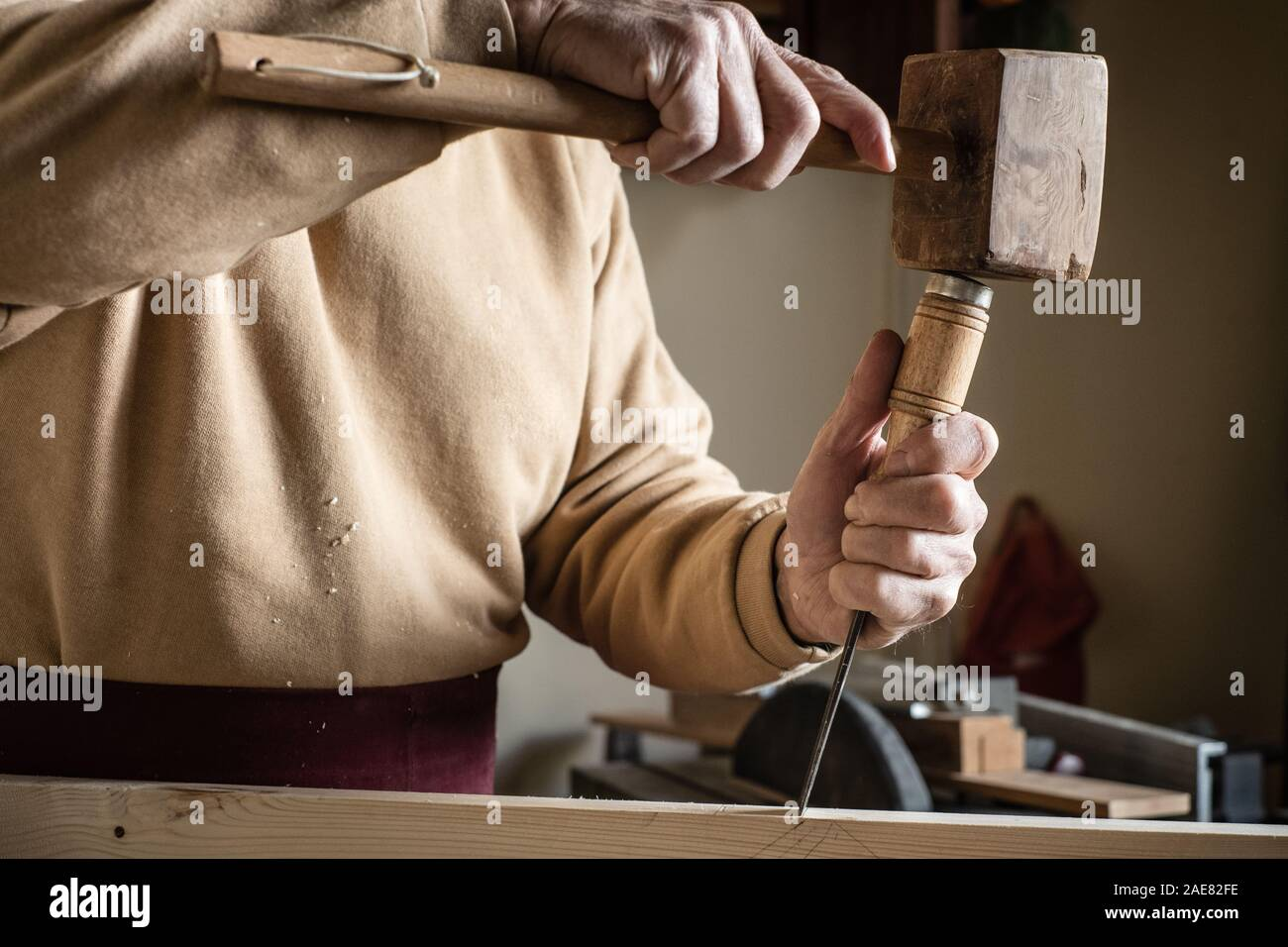 Carpenter working with a wooden hammer and a gouge Stock Photo