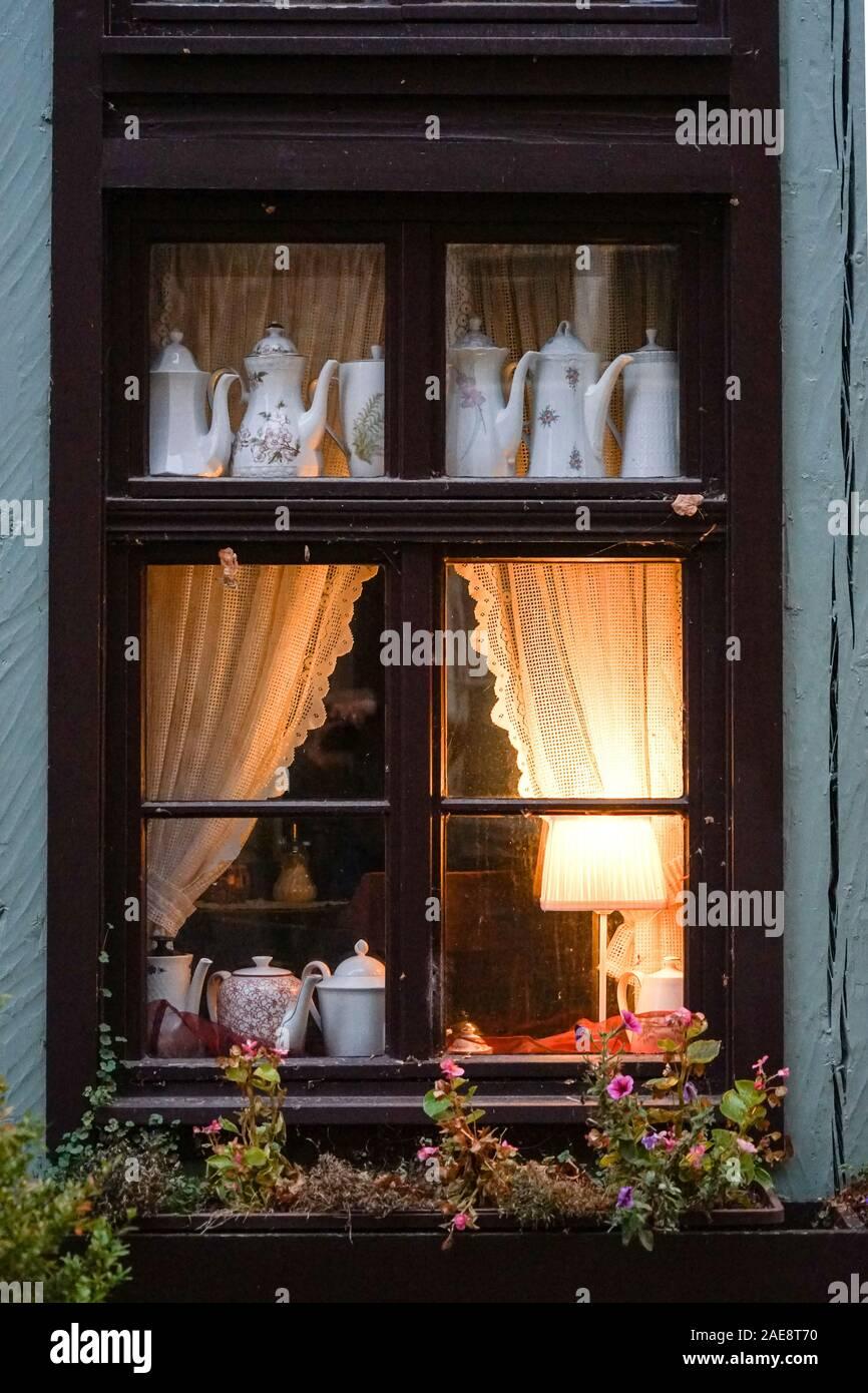 Warmly lit window in a dark wintry lane Stock Photo