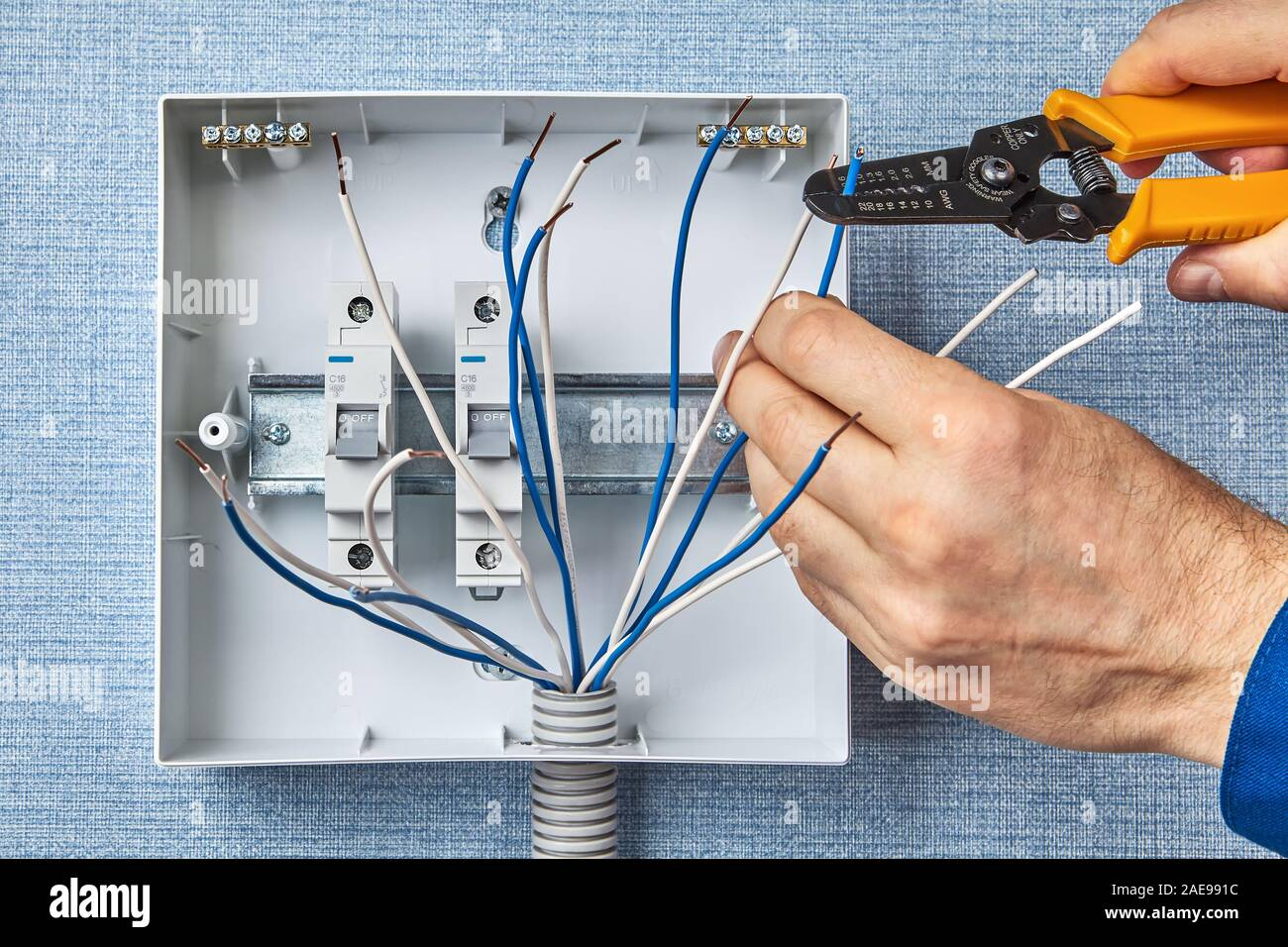 An electrician uses a instrument to remove insulation from ... on