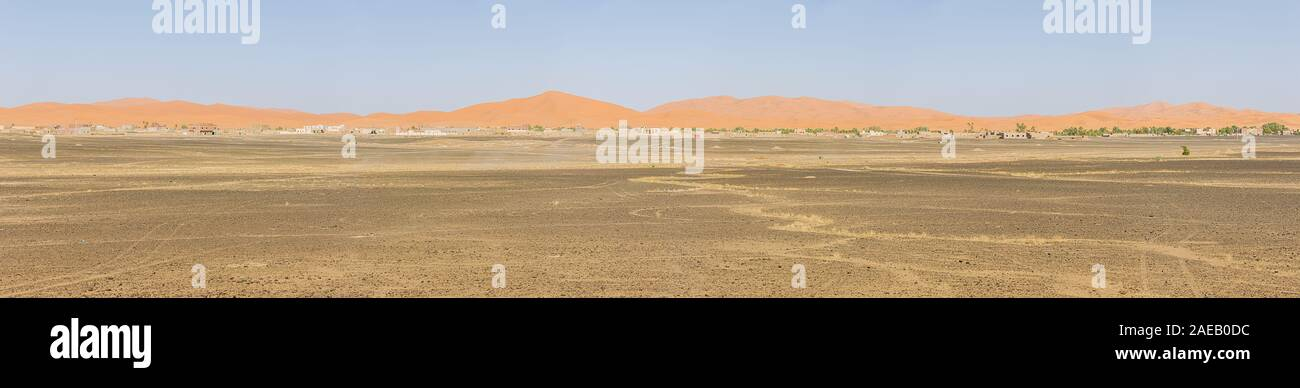 Panorama of the sand dunes of Erg Chebbi with Merzuga in the foreground Stock Photo