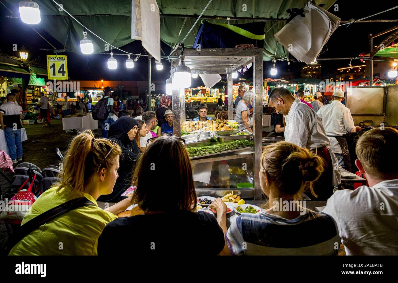 Tourists enjoy the meal around the long trestle tables,at night in Jemaa el-Fnaa or  Djema el-Fna  market square.Medina of Marrakesh,Morocco Stock Photo