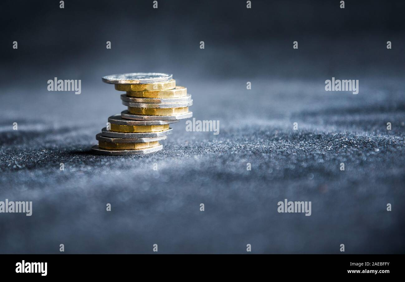British one pound sterling coins stack isolated on dark background - money concept, economy, financial crisis, debit card, credit card, mortgage Stock Photo