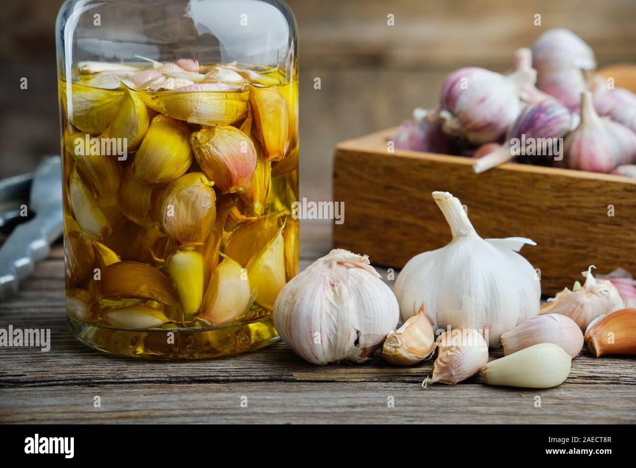 Garlic aromatic flavored oil or infusion bottle and wooden crate of garlic cloves on wooden kitchen table. Stock Photo