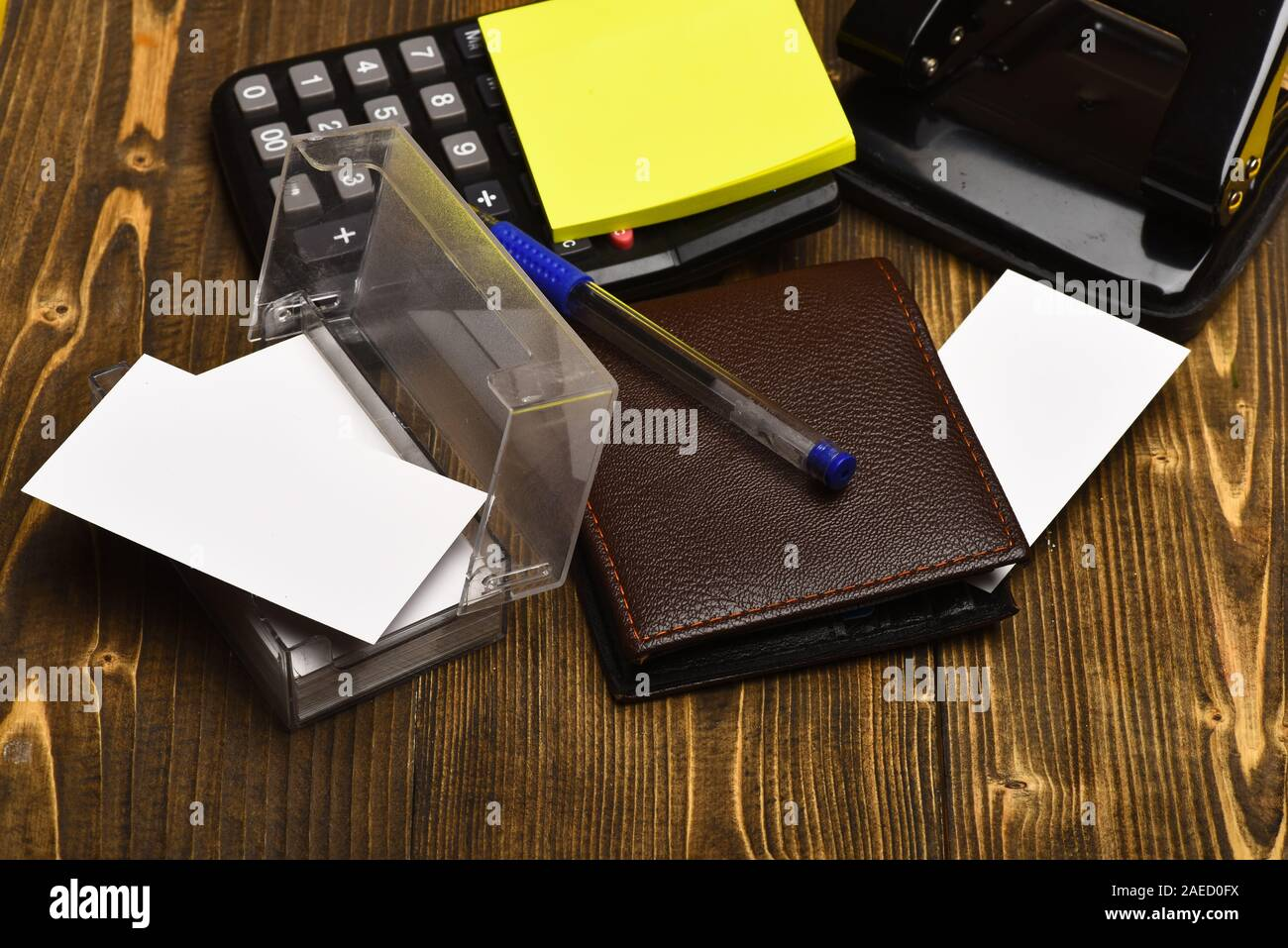 Business and work concept. Calculator, hole punch, business card holder, note paper and pen. Mans leather wallet and stationery. Office tools isolated on vintage background, close up. Stock Photo