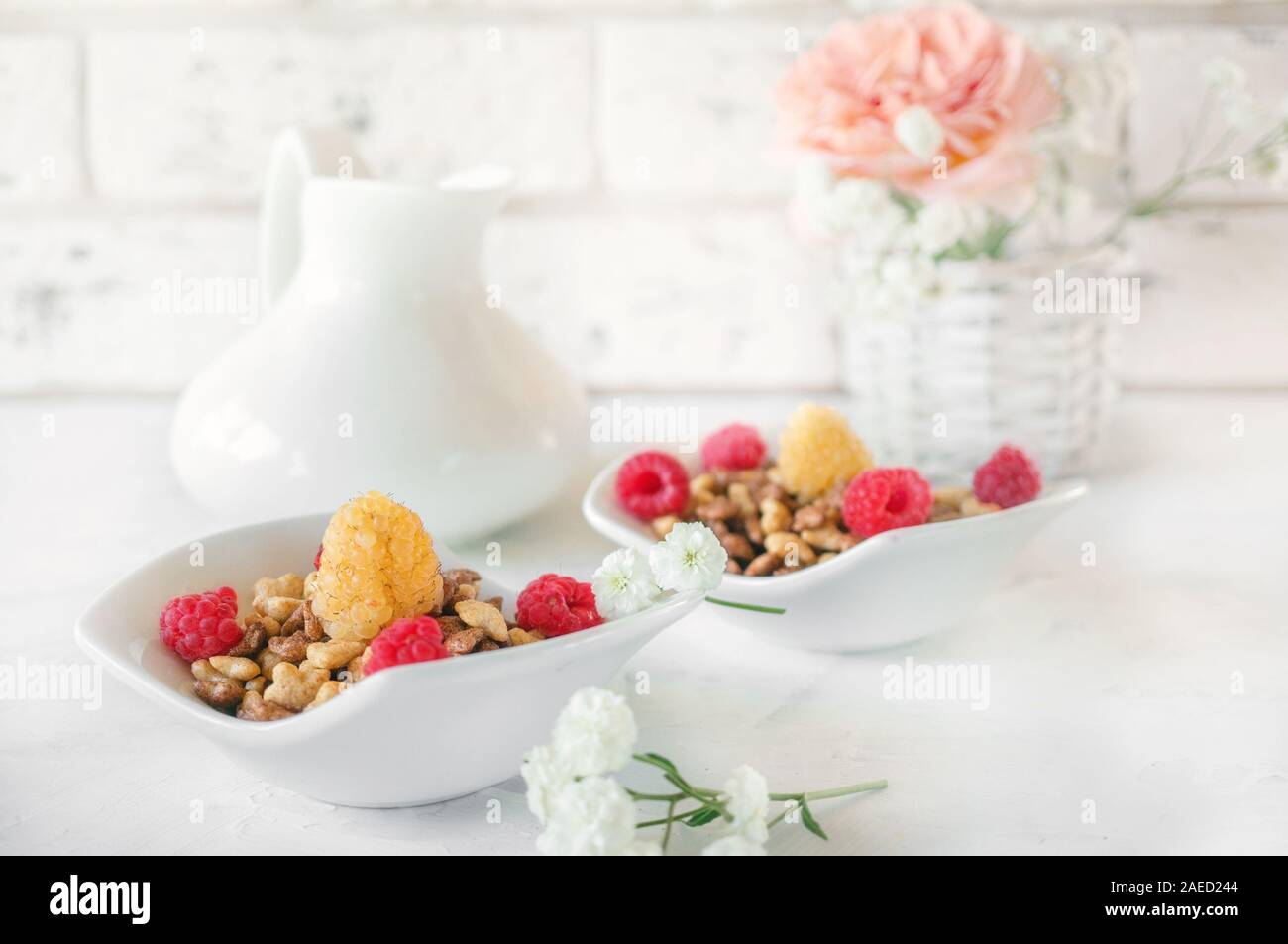 Organic muesli with raspberries for Breakfast in a white porcelain Cup with small white flowers on a light background. Stock Photo
