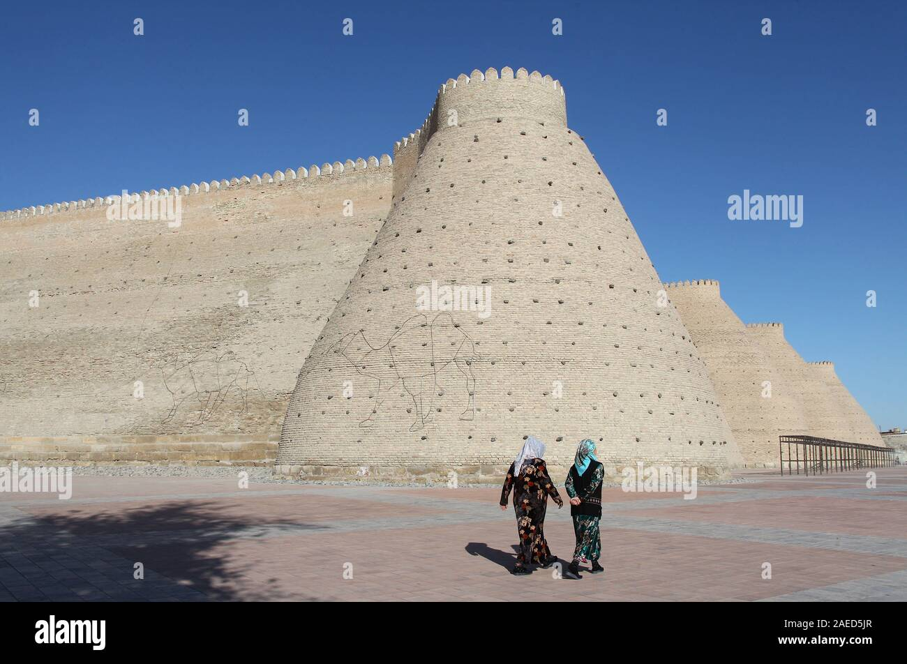Local women walking past the historic walls of the Ark Fortress Stock Photo