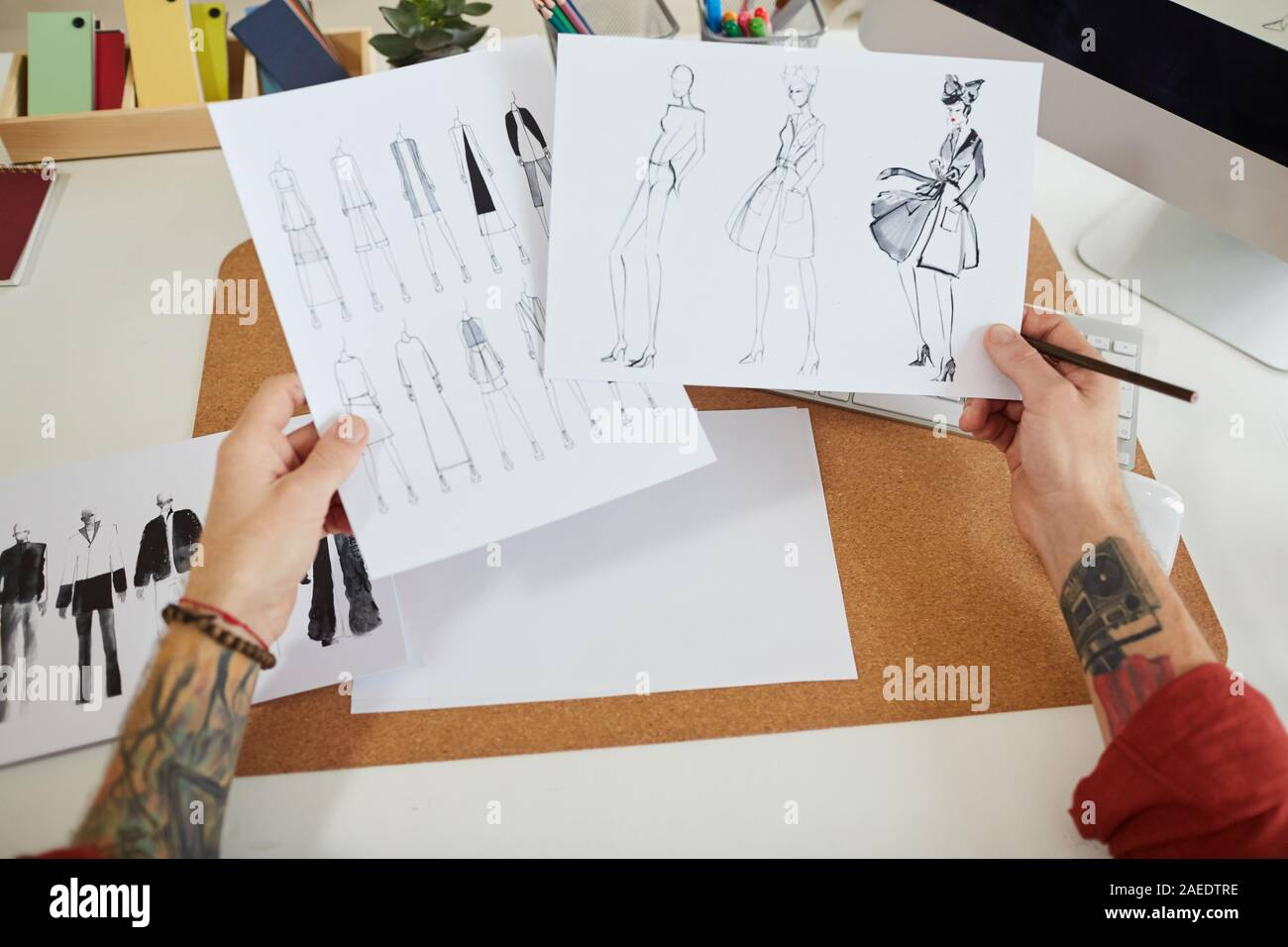 Close Up Of Tattooed Male Hands Holding Fashion Sketches Over Workplace In Design Studio Copy Space Stock Photo Alamy