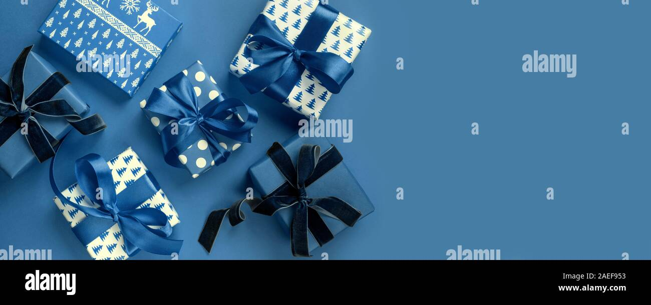 Christmas banner of holiday gifts on blue background. Boxing day. Greeting card. Winter. Happy New Year. View from above, flat lay. Template, mockup. Stock Photo